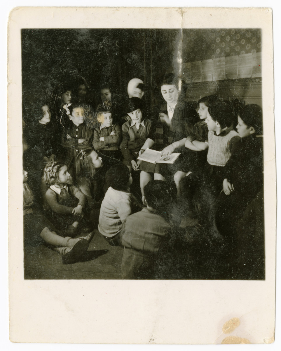 A woman reads aloud to a group of children in the OSE Taverny children's home..