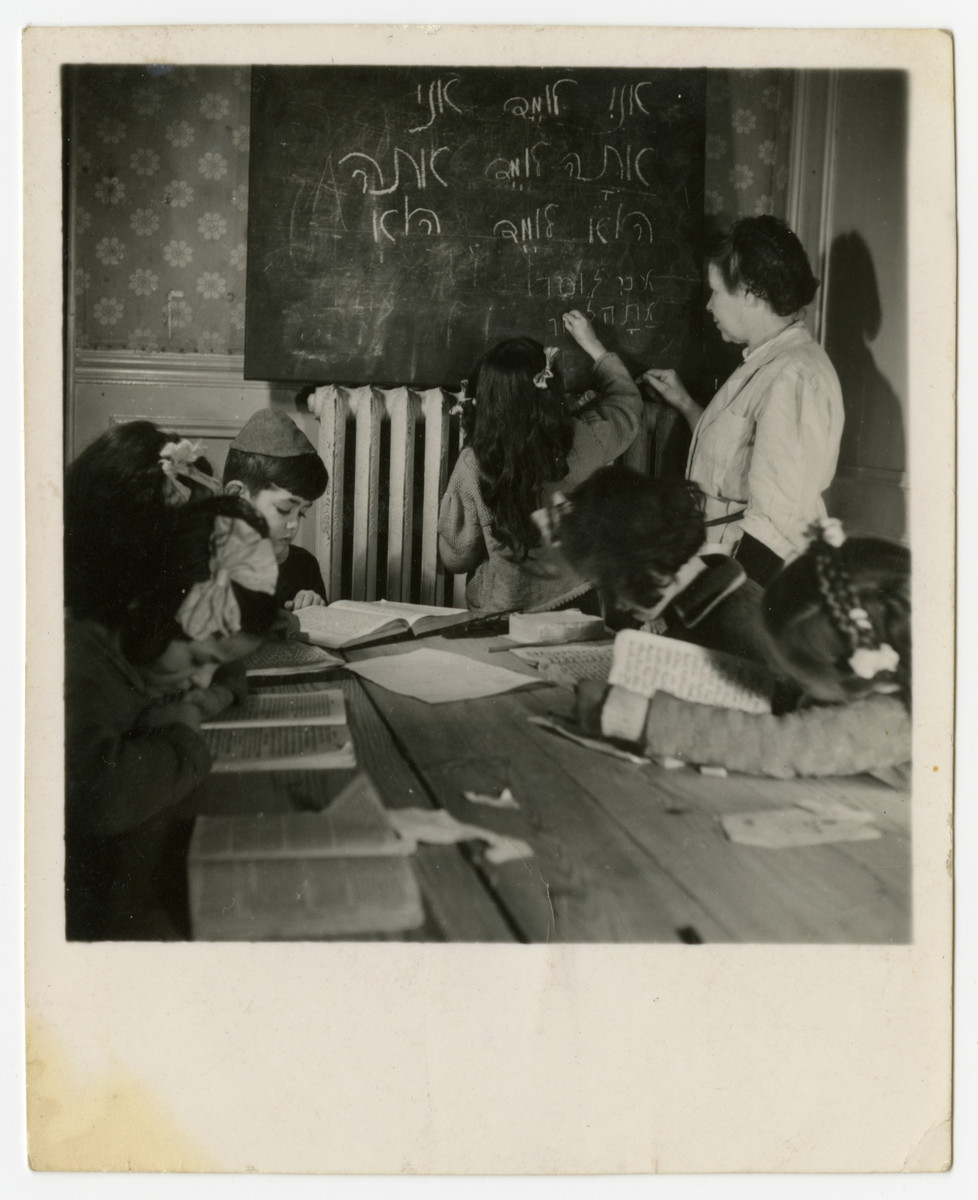 Children study Hebrew in the Taverny OSE children's home.  Felice Zimmern is pictured with her head on the table.