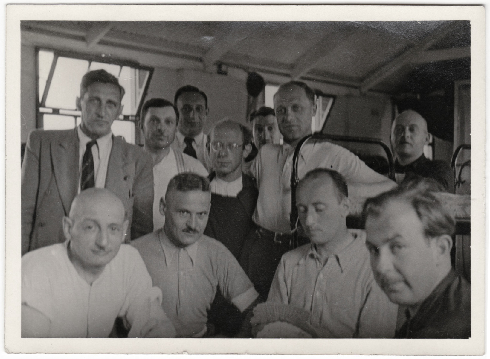 Group portrait of Jewish men inside a barracks in the Kitchener refugee camp.  Siegfried Kulmann is pictured in the lower right.