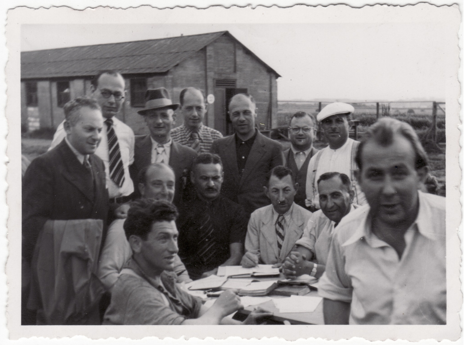 Jewish men gather around an outdoor table in the Kitchener refugee camp.  Siegfried Kulmann is pictured in the lower right wearing a white short sleeve shirt.