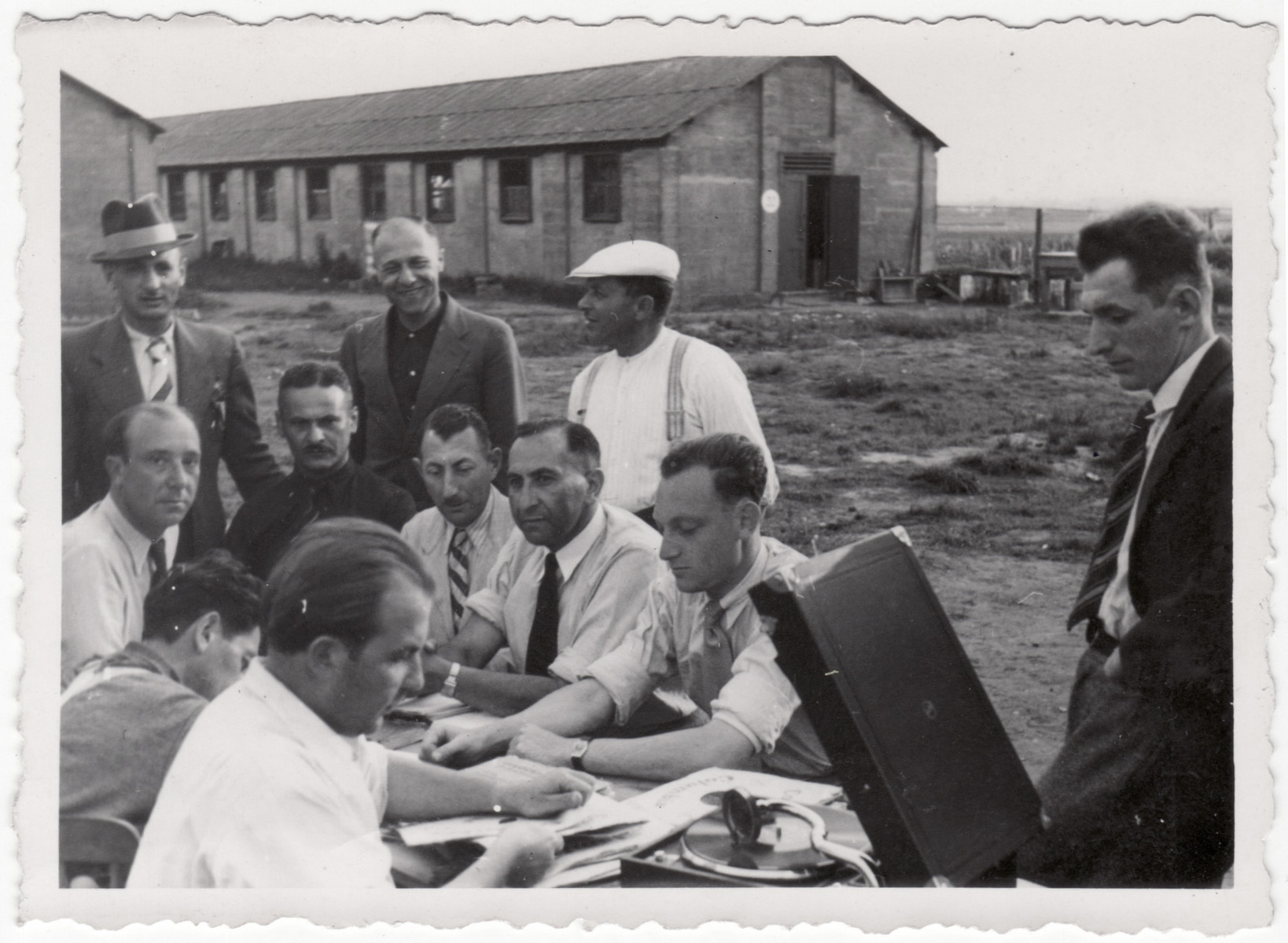 Jewish refugees gather by an open briefcase on an outdoor table at the Kitchener refugee camp.  Siegfried Kulmann is pictured in the lower left in a white short sleeve shirt taking out a record for the record player.