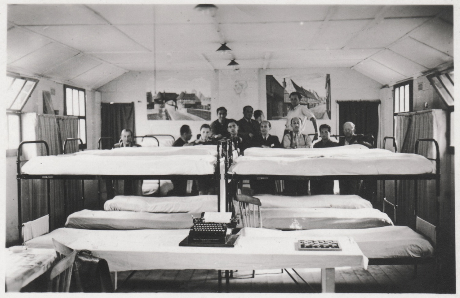 Jewish refugees pose behind their bunk beds in a barracks in the Kitchener refugee camp.