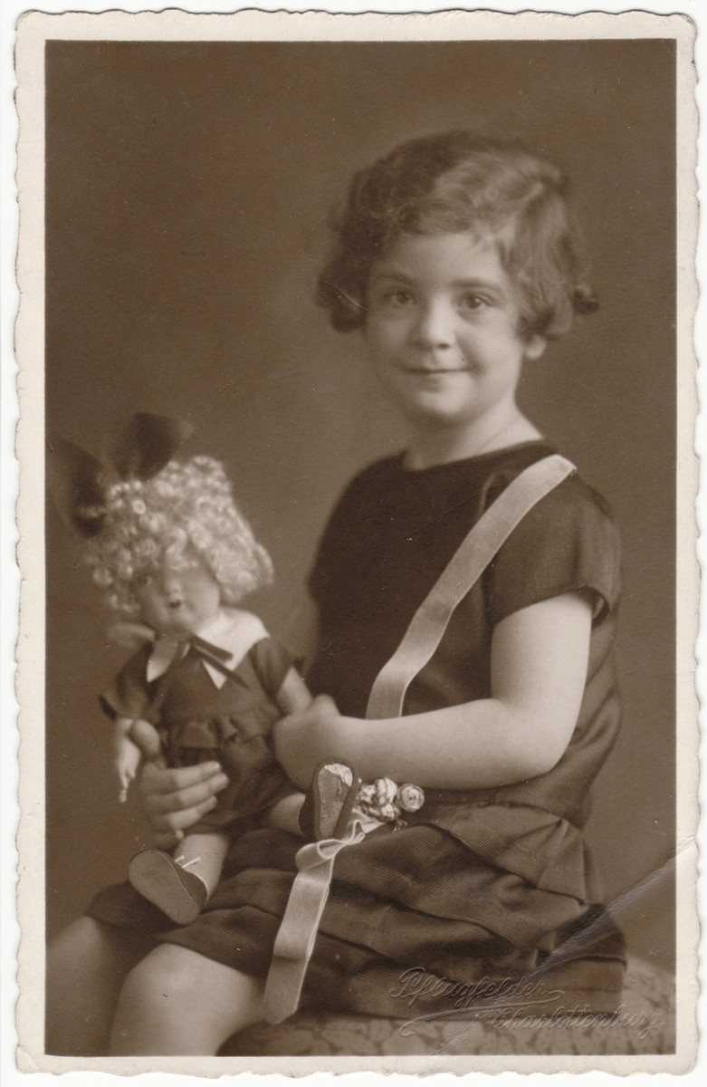 Studio portrait of four-year-old Marion Bassfreund holding her doll.