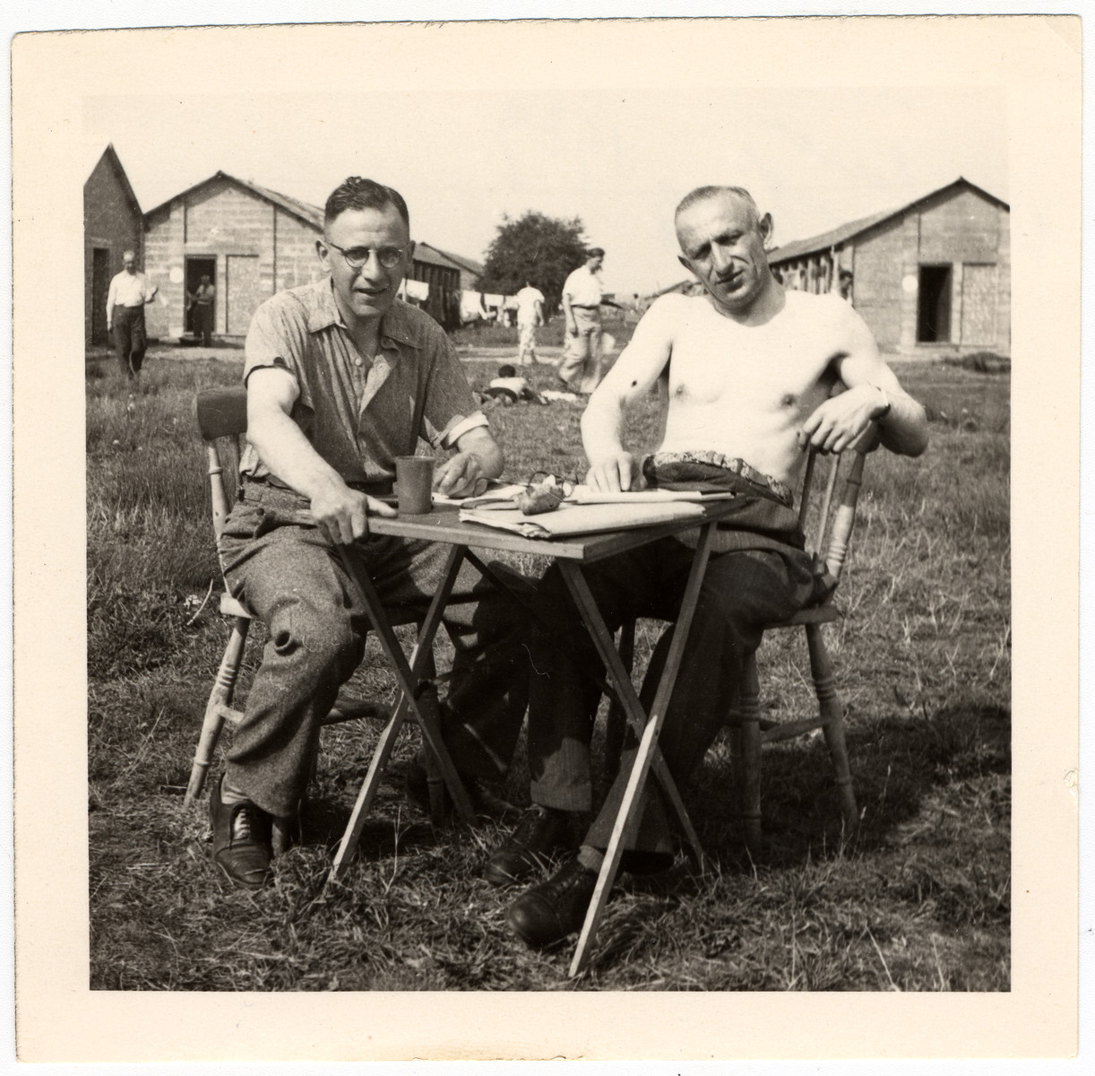 Herbert Hoexter and another gentleman sit outside at a small table in the Kitchener refugee camp.