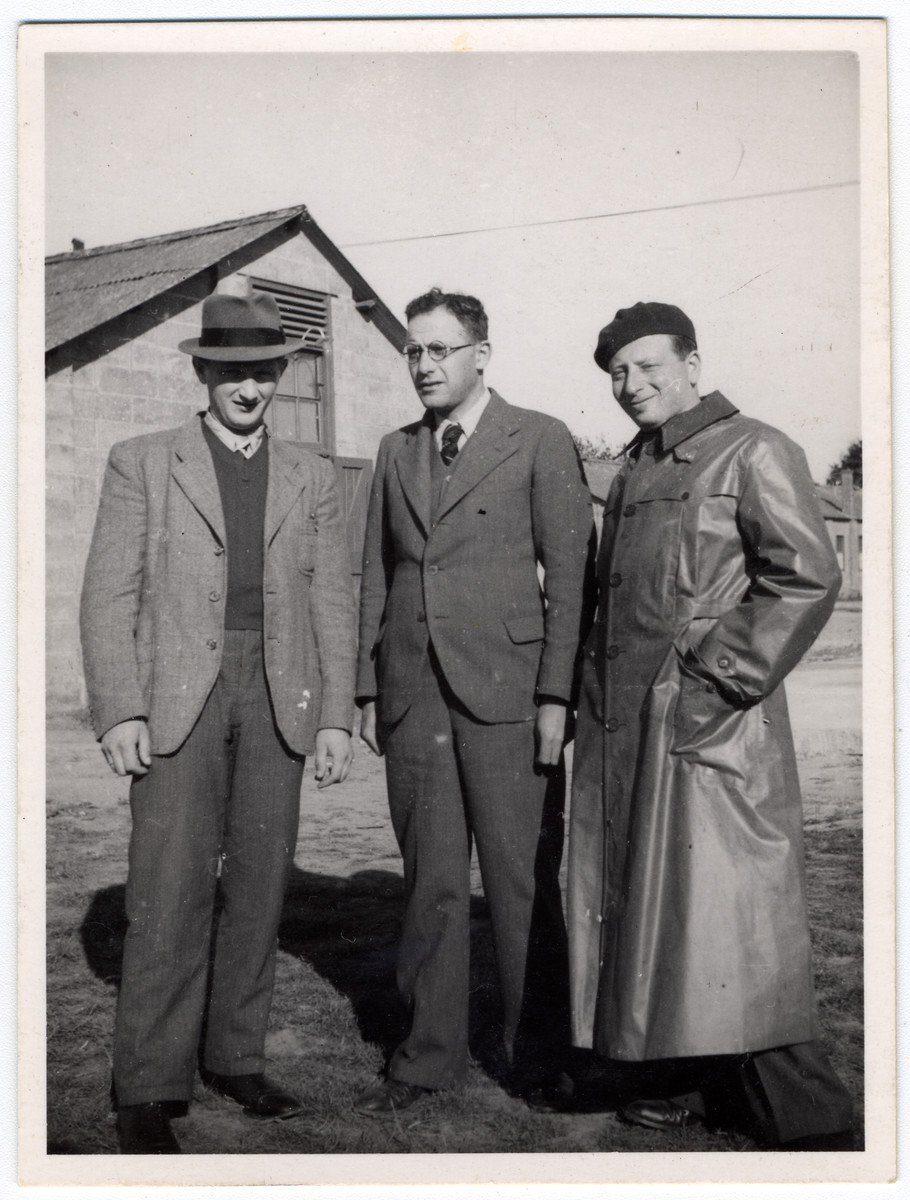 Three German-Jewish refugees stand in front of a barracks in the Kitchener camp.  Herbert Hoexter is pictured in the center.