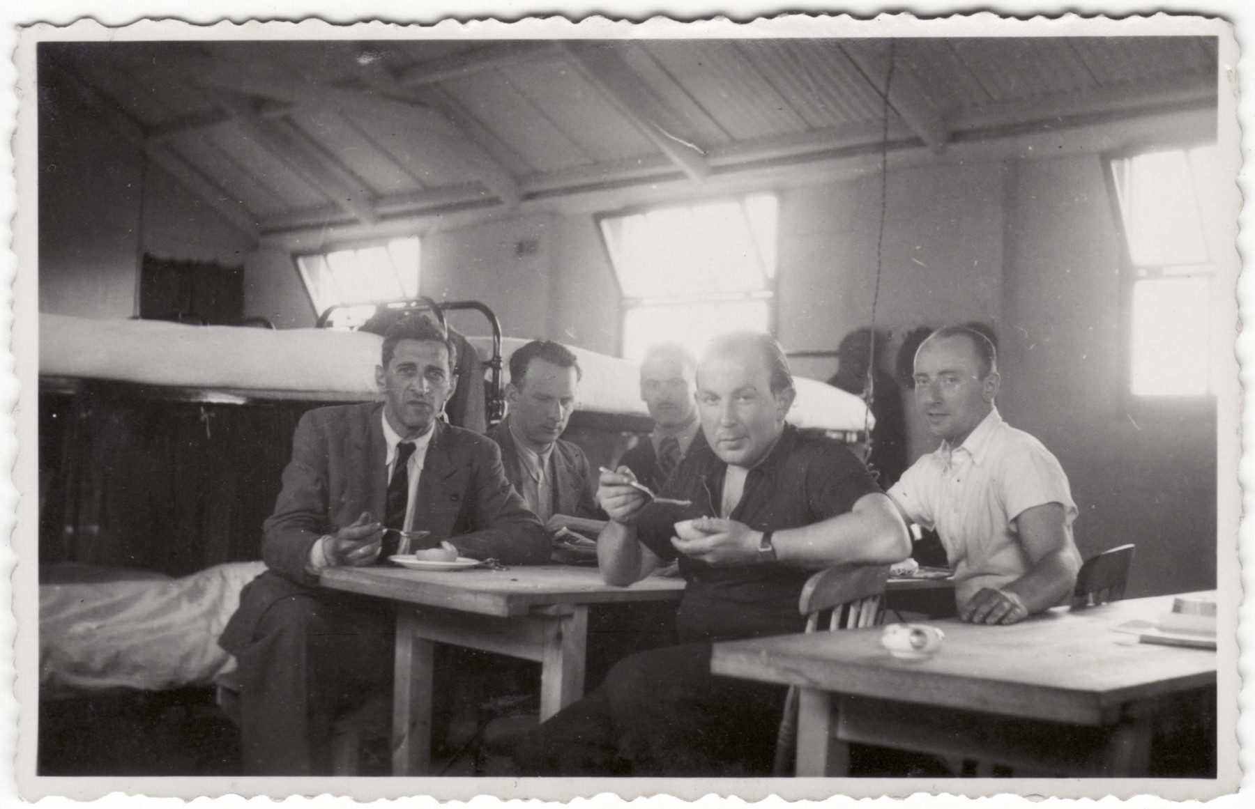 Jewish refugees eat a meal in their barracks in the Kitchener refugee camp.  Siegfried Kulmann is pictured second from the right.