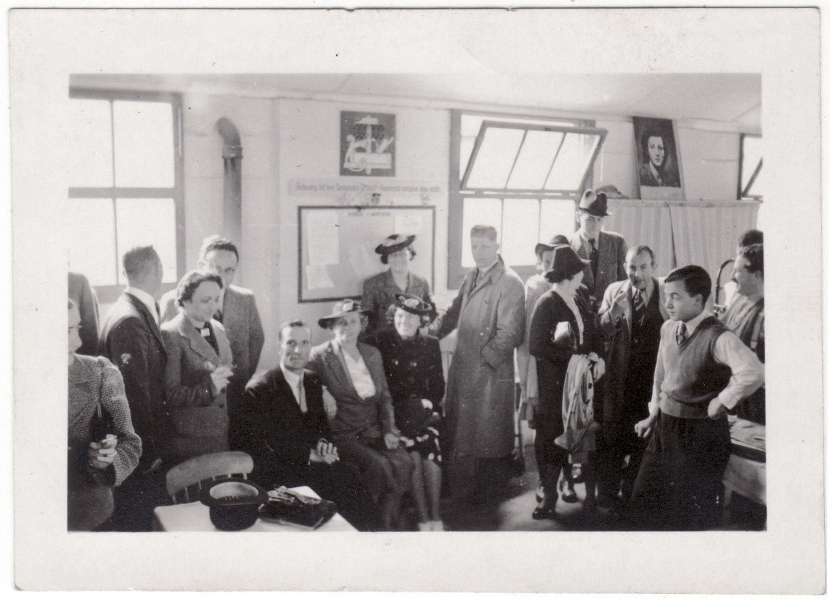 Jewish refugees gather and socialize inside a building of the Kitchener refugee camp.  Among those pictured are Sydney Kulmann (third from the right facing the camera) and [possibly his fiancee Marion Bassfreund] next to him.