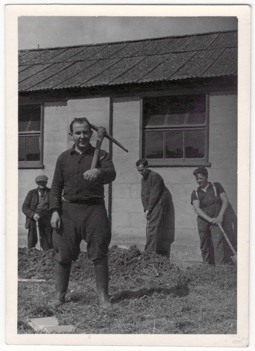 Siegfried Kulmann carries a pick axe in the Kitchener refugee camp where he had to work the land as an introduction into the British way of life.