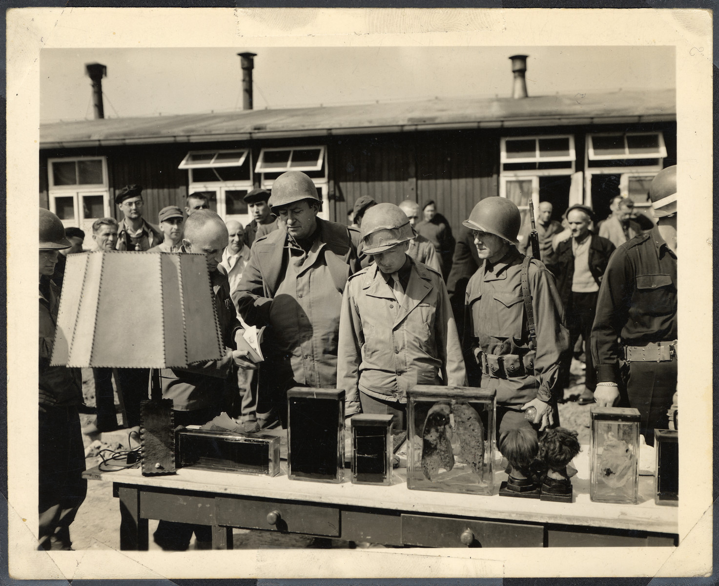 Members of General Patton's Third Army view articles made of prisoner remains as survivors watch. Seen here are lamp shades and book bindings allegedly made from human flesh, preserved human organs, and wigs.