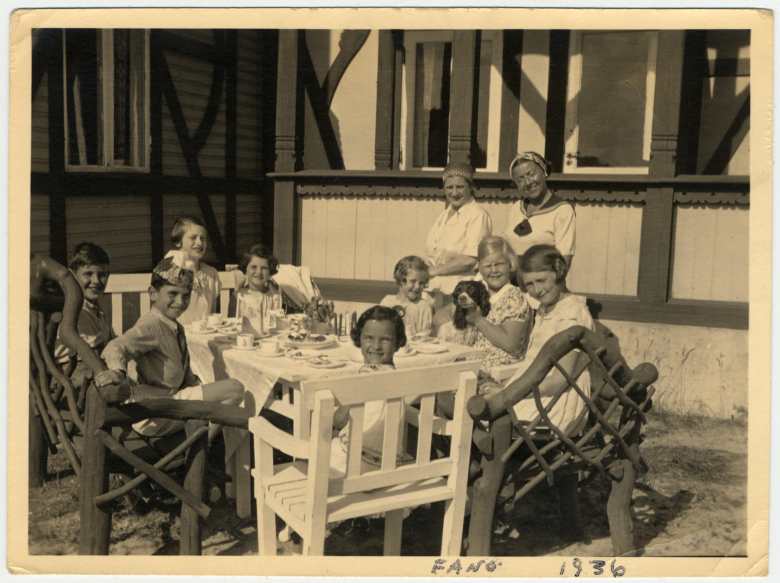 Young children attend a party.  Among those pictured are Gerald Liebenau (front left) and his mother Helene (standing far right). Gerald's sister, Irene, sits directly across the table from him. Her birthday is in July and this could have been a birthday party for her. The picture was taken during a summer holiday on the island of Fanoe, Denmark.