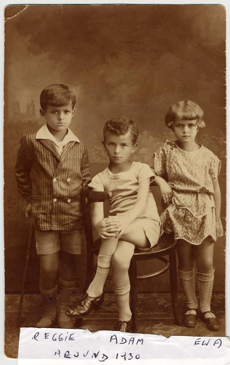 Studio portrait of three Polish Jewish children: Ignacy (Reggie) Wistreich, Adam Kahane, and Eva Wistreich.