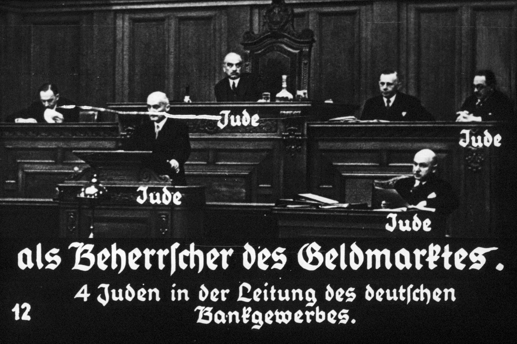 "12th Nazi propaganda slide of a Hitler Youth educational presentation entitled ""Germany Overcomes Jewry.""  als Beherrscher des Geldmarktes. 4 Juden in der Leitung des deutschen Bankgewerbes. // Commander of the money market. Four Jews in the leadership of the German banking industry."