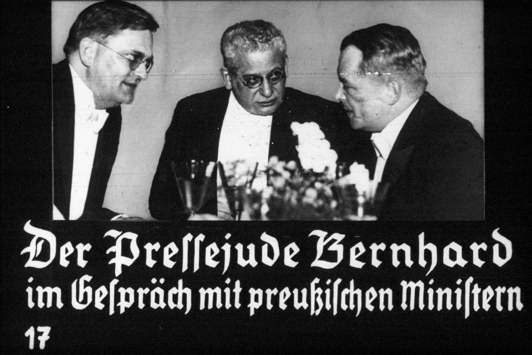 "17th Nazi propaganda slide of a Hitler Youth educational presentation entitled ""Germany Overcomes Jewry.""  Der Pressejude Bernhard im Gespräch mit preußischen Ministern. // The Jewish journalist Bernhard interviews Prussian ministers."