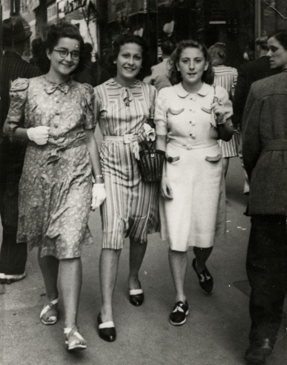 Three friends from the Eclaireurs Unionistes walk down a street in Marseilles.  Pictured are Denise Caraco (center) with Monique (left) and Juliette Beltrando (right).