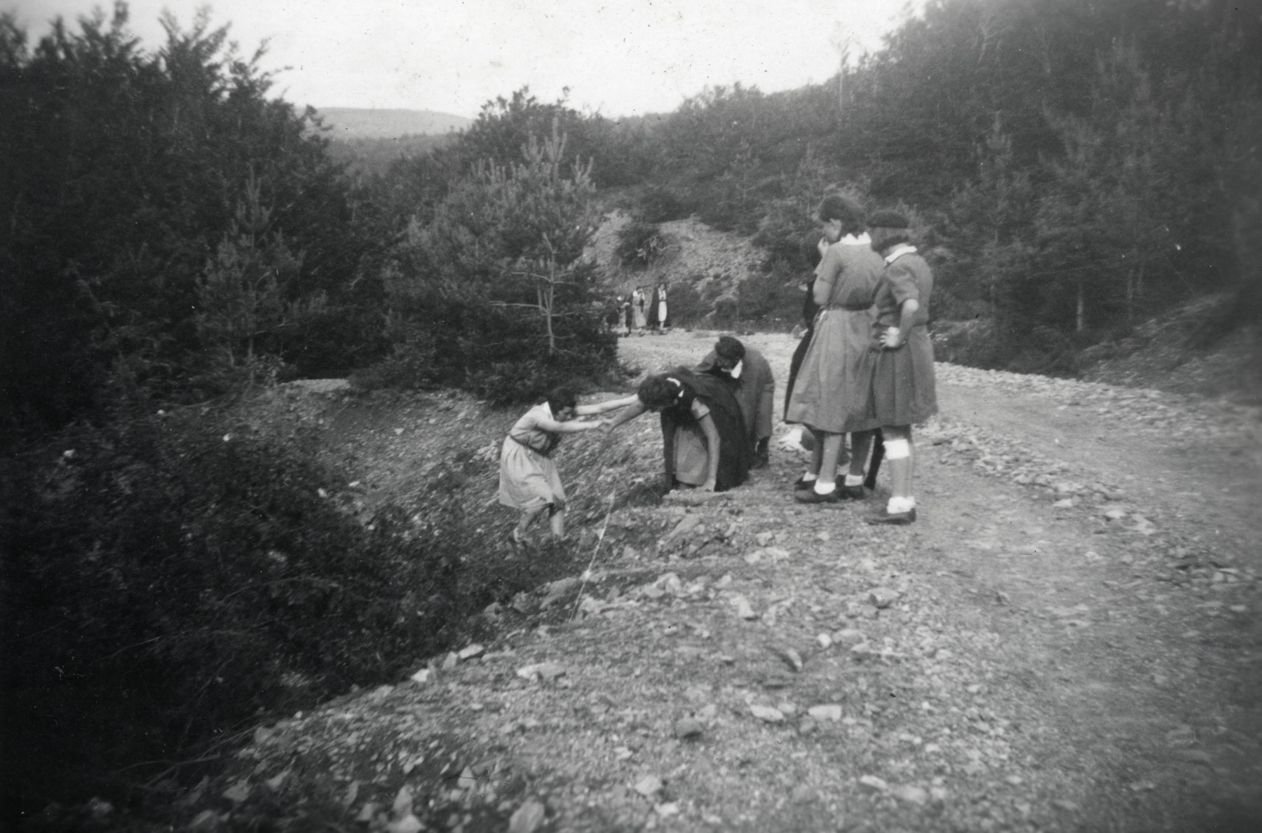 Two girls help a friend climb up the roadside along a dirt road while a few other girls are watching. They attended the Eclaireurs Unionistes summer camp.