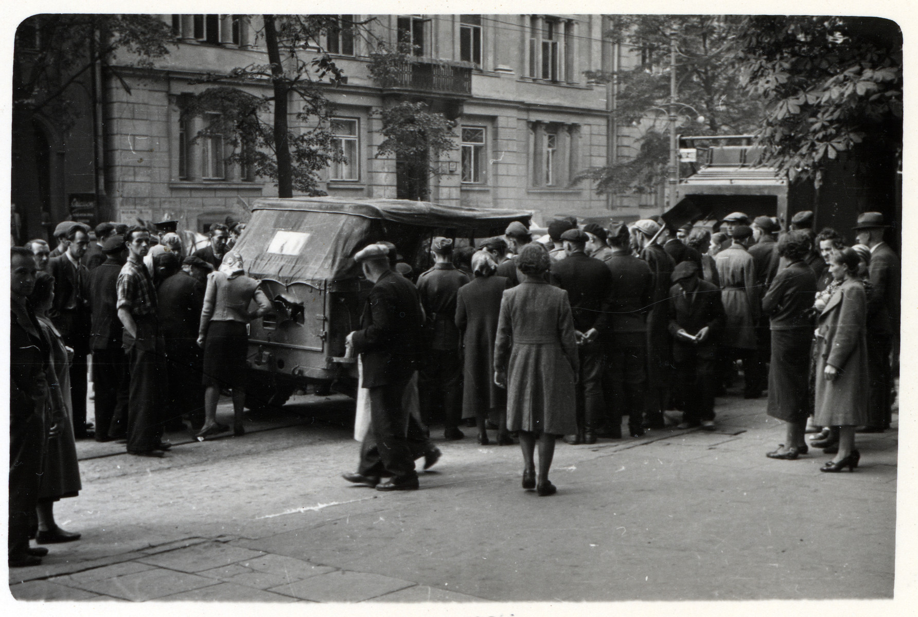 A crowd of Polish spectators surround military vehicles on a street in Poland.