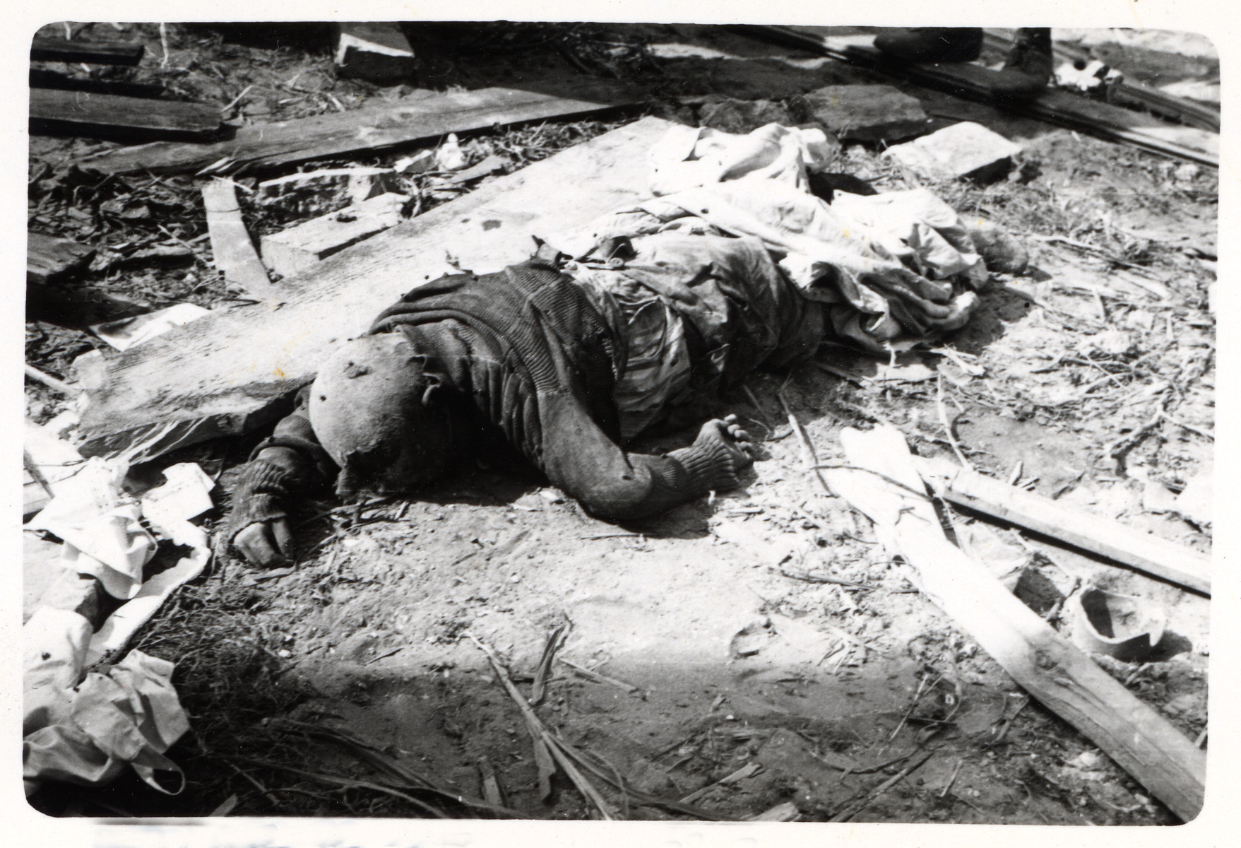The corpse of a  child lies on the grounds of a bombed out school in besieged Warsaw.
