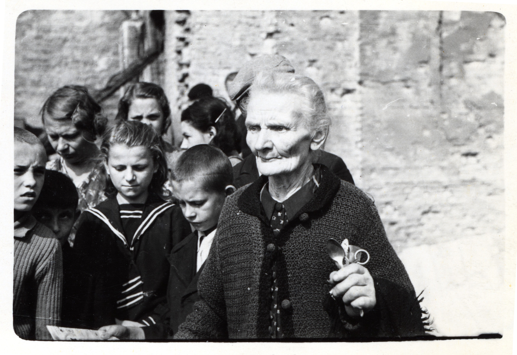An elderly Polish woman, standing in front of a group of children, holds two silver spoons and a pair of scissors, all that remained of her home after it was destroyed in a German air raid during the siege of Warsaw.  The woman's name is Mrs. Jaworska.  Julien Bryan later learned that she died in 1940.