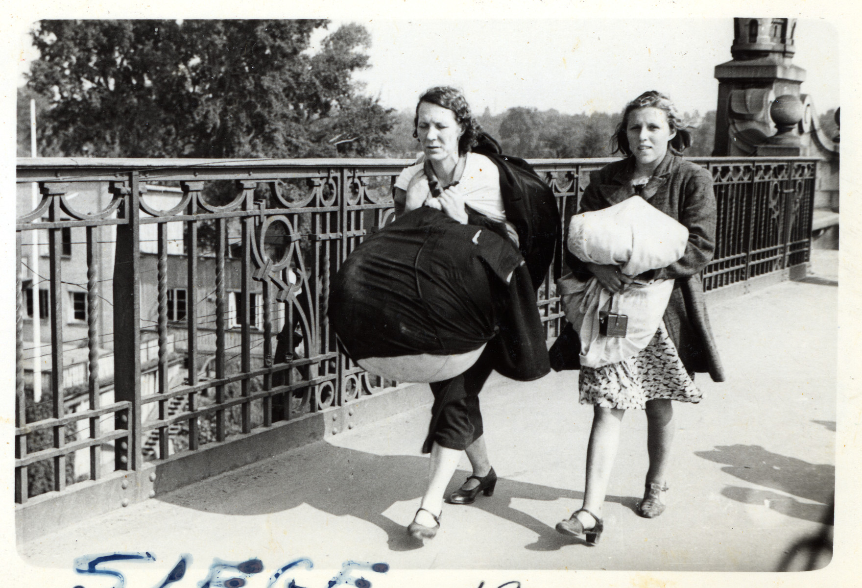 A Polish mother and daughter flee the besieged city of Warsaw with bedding and other essential household items.