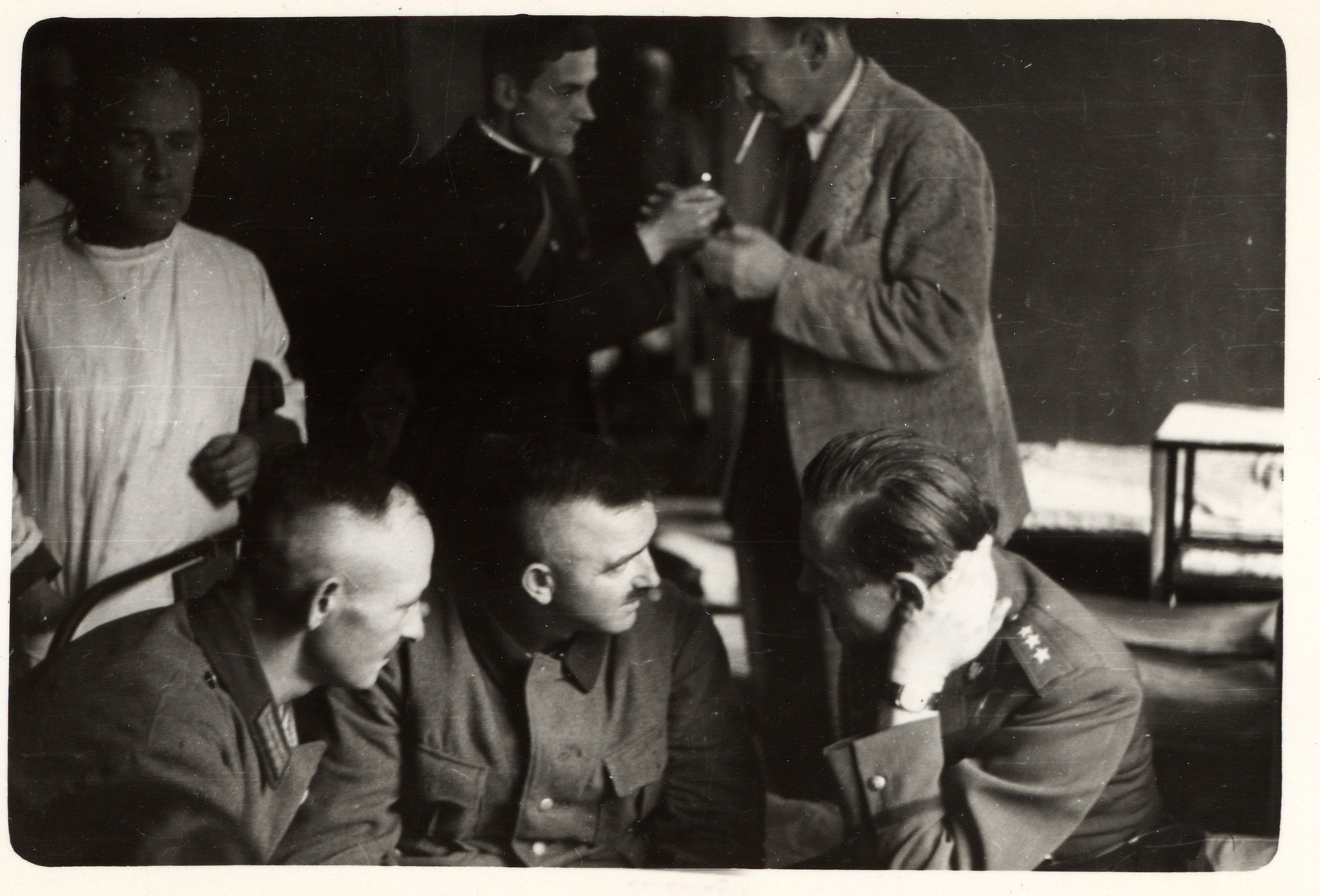 German POWs discuss amongst themselves while a Polish priest lights Julien Bryan's cigarette in the background.