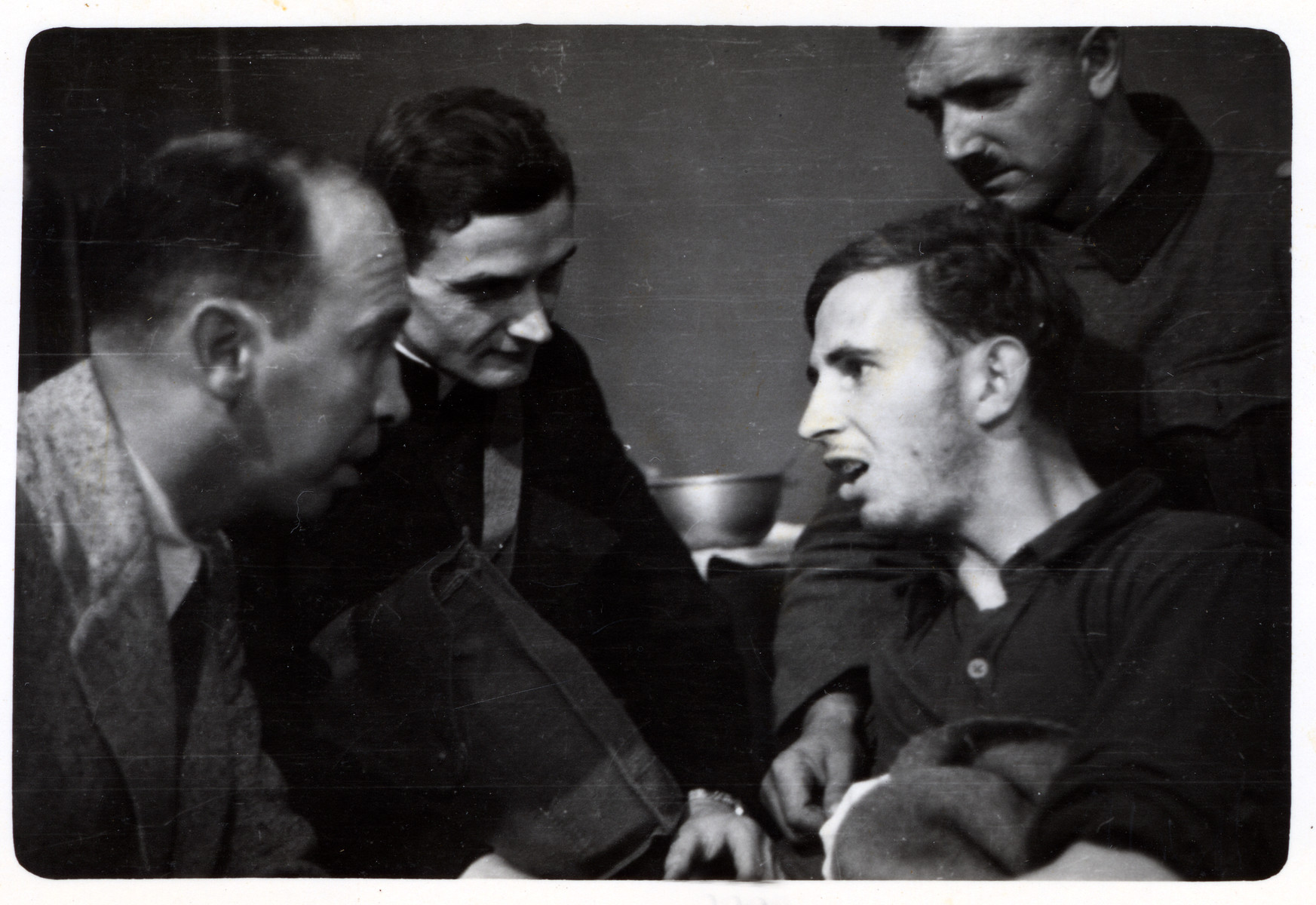 A polish priest and Julien Bryan visit a wounded German POW in besieged Warsaw.