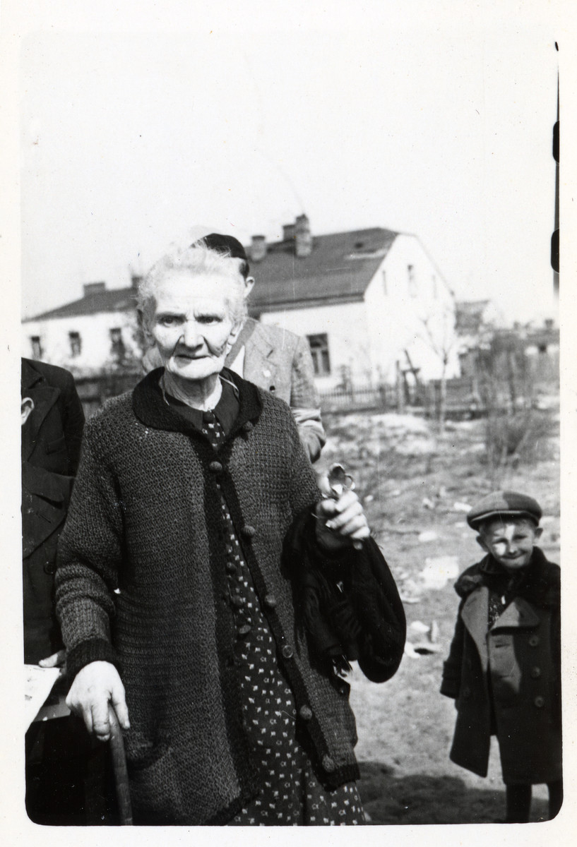 An elderly Polish woman holds two silver spoons and a pair of scissors, all that remained of her home after it was destroyed in a German air raid during the siege of Warsaw.  The woman's name is Mrs. Jaworska.  Julien Bryan later learned that she died in 1940.