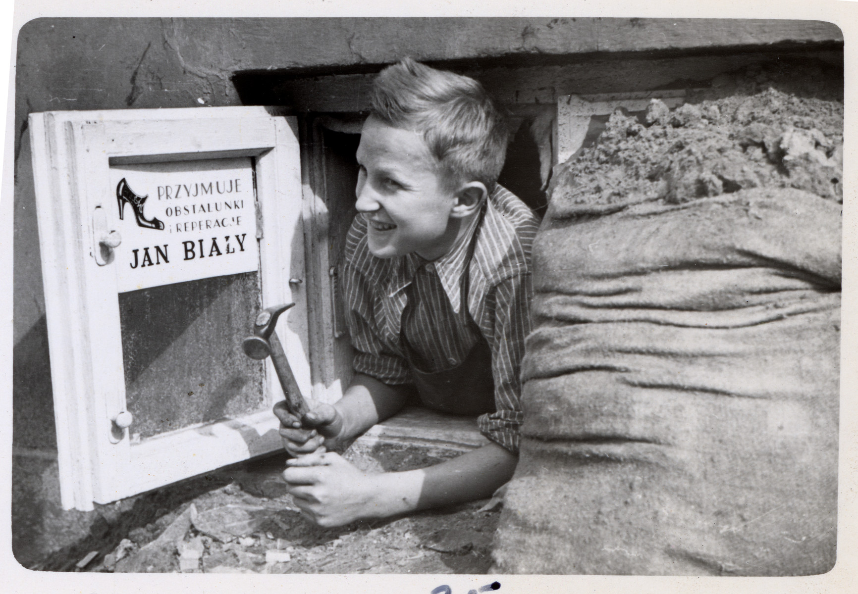 A young Polish cobbler looks out his window in Poland.