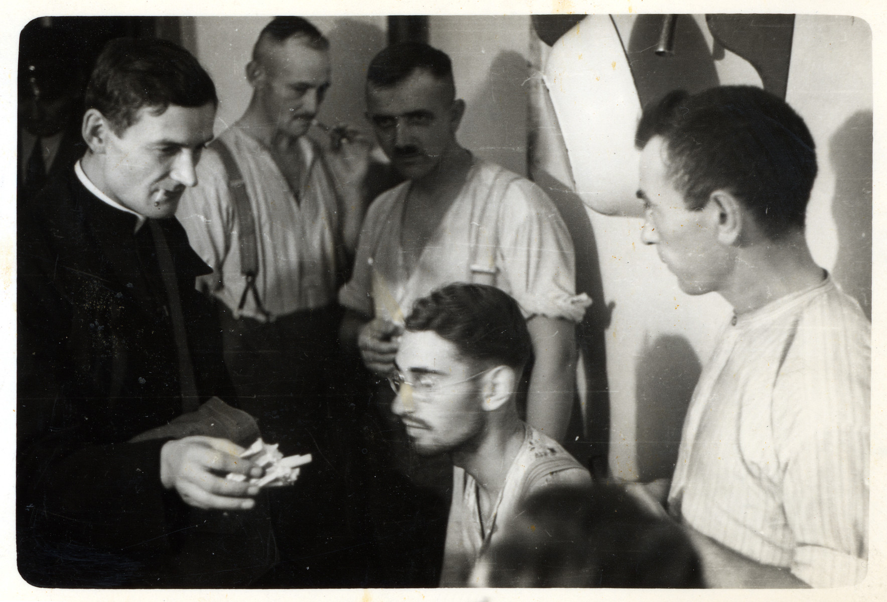 A Polish priest offers cigarettes to German POWs.