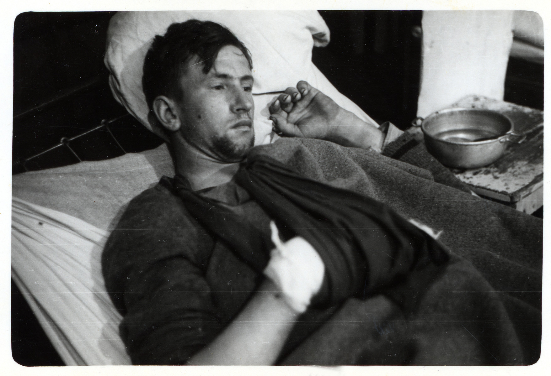 A wounded German POW rests in a hospital bed.