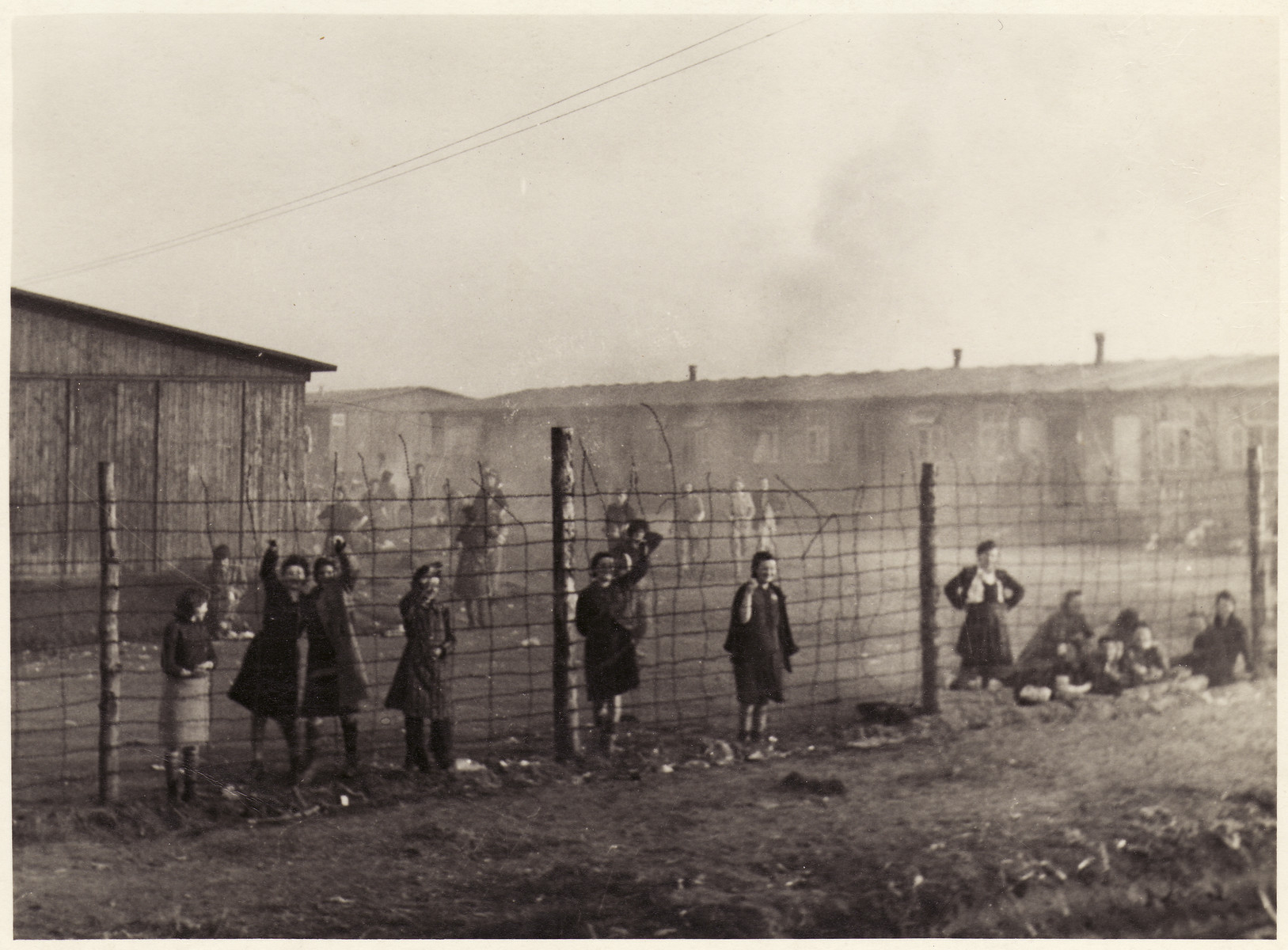 Women survivors of the Bergen-Belsen concentration camp stand and sit behind the fence of the camp.