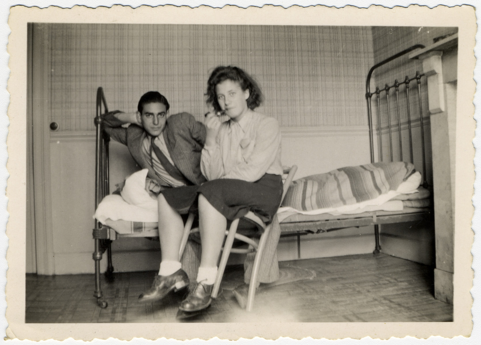 Two Jewish young people pose in a room with a bed and chair.  Pictured are Haim Vidal Sephiha and Ida (Naomi) Rosenschtraugh.  She later immigrated to Israel.