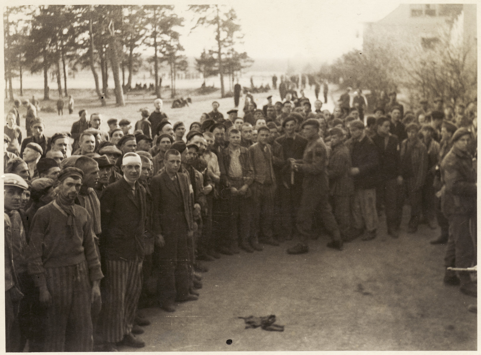 Survivors stand outside at the Bergen-Belsen concentration camp while British soldiers walk and stand among them.