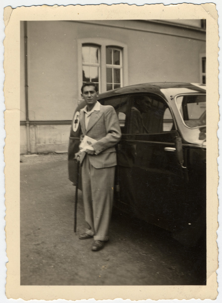 "Jacques Sephiha poses with a cane next to an ambulance after his return to Belgium from his hospitalization in a sanatorium in Switzerland following his liberation from concentration camp.  His original caption reads ""Far from your eyes, but close to your heart, your little brother Jacques."""