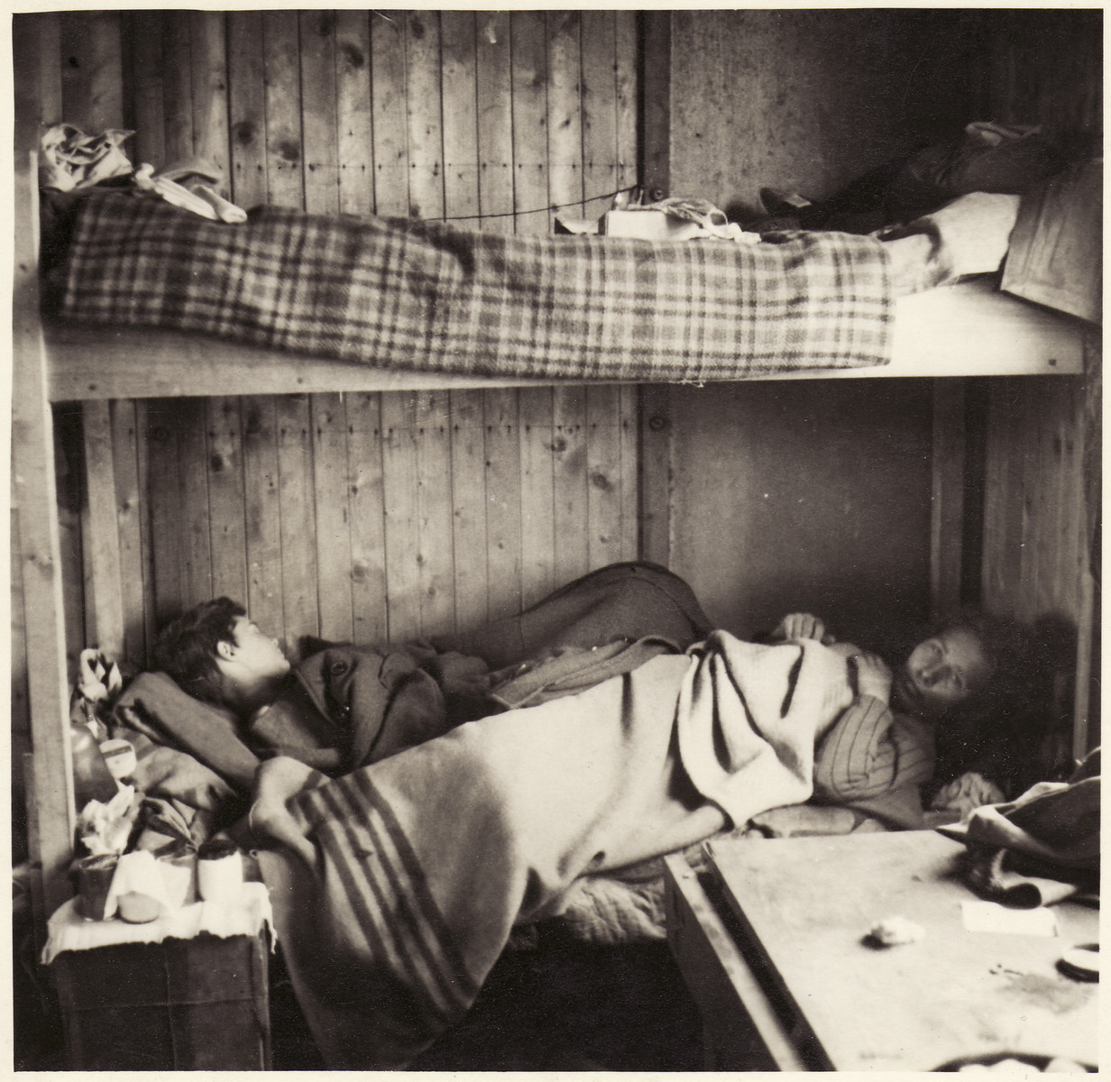 A woman and young boy lie on the bottom bunk inside a barrack at the Bergen-Belsen concentration camp.