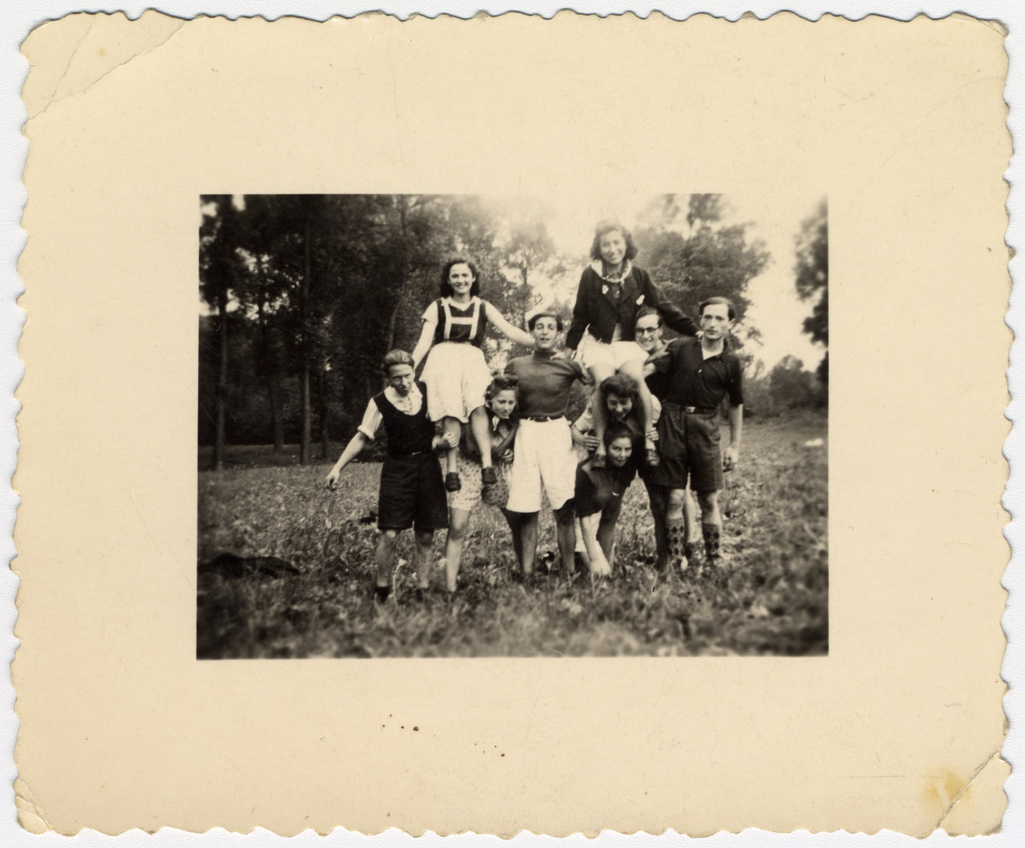 Students in La Ramee agricultural school pose, some on each other's shoulders.  Haim Sephia is pictured standing in the center.  Also picured are Shulinski (left), Paulette Weinstadt, Simone Firminski, Eva and Charles Lishinski.  Sitting on shoulders are Marie and Basia.  Simone Firminski and Marie were deported.