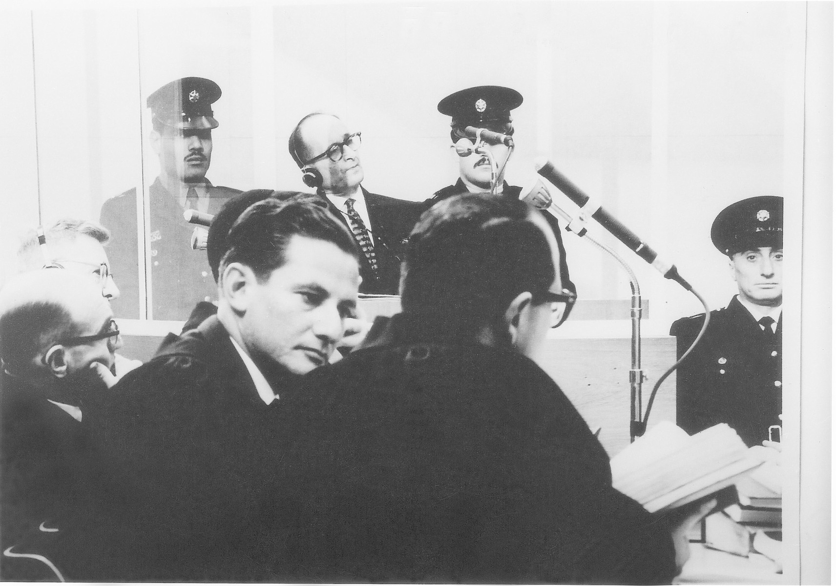 Adolf Eichmann listens to the proceedings through a glass booth during his trial in Jerusalem.