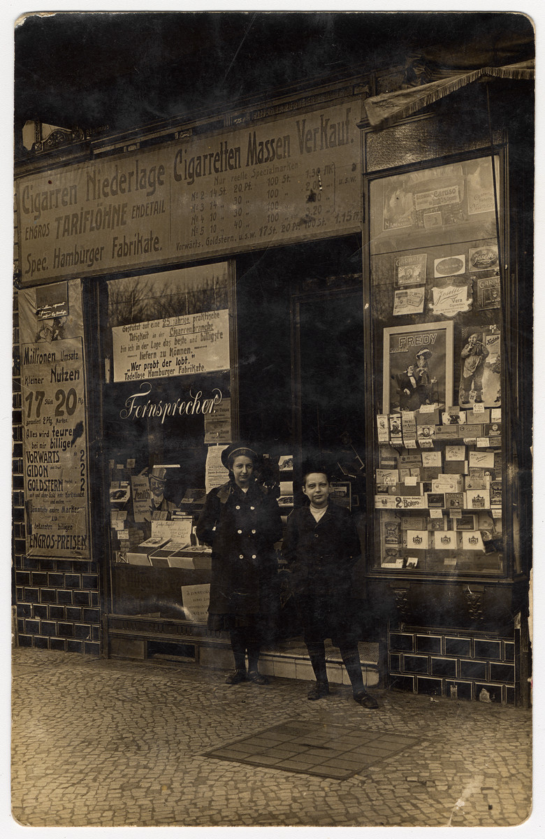 A brother and sister pose in front of their father's cigar store.  Pictured are Augusta and Karl Brager.