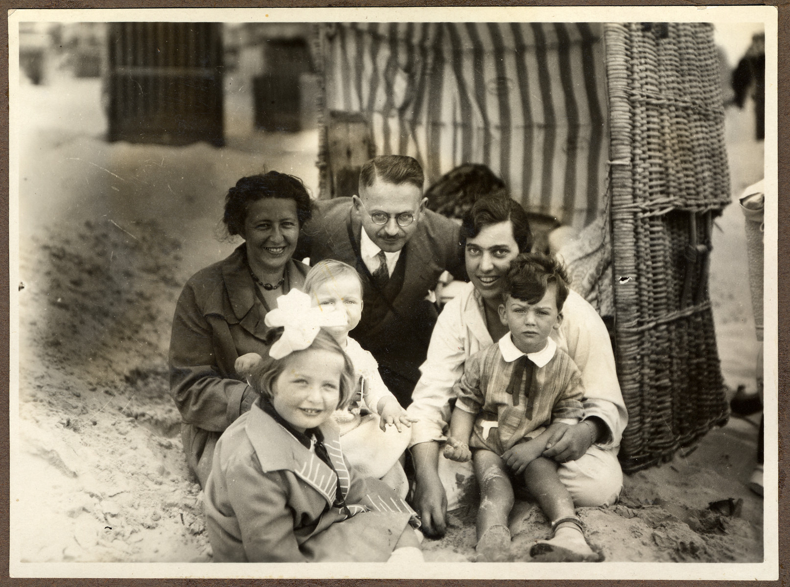 A German-Jewish family relaxes on the beach in front of a cabana.  Helga Bujakowski is seated in the front left.  Her mother Augusta is behind her.  Her father, Dr. Hans Adolf Bujakowski is in the center.  On the right are Rute Fiegel with her son Gerhard and daughter Ellen.