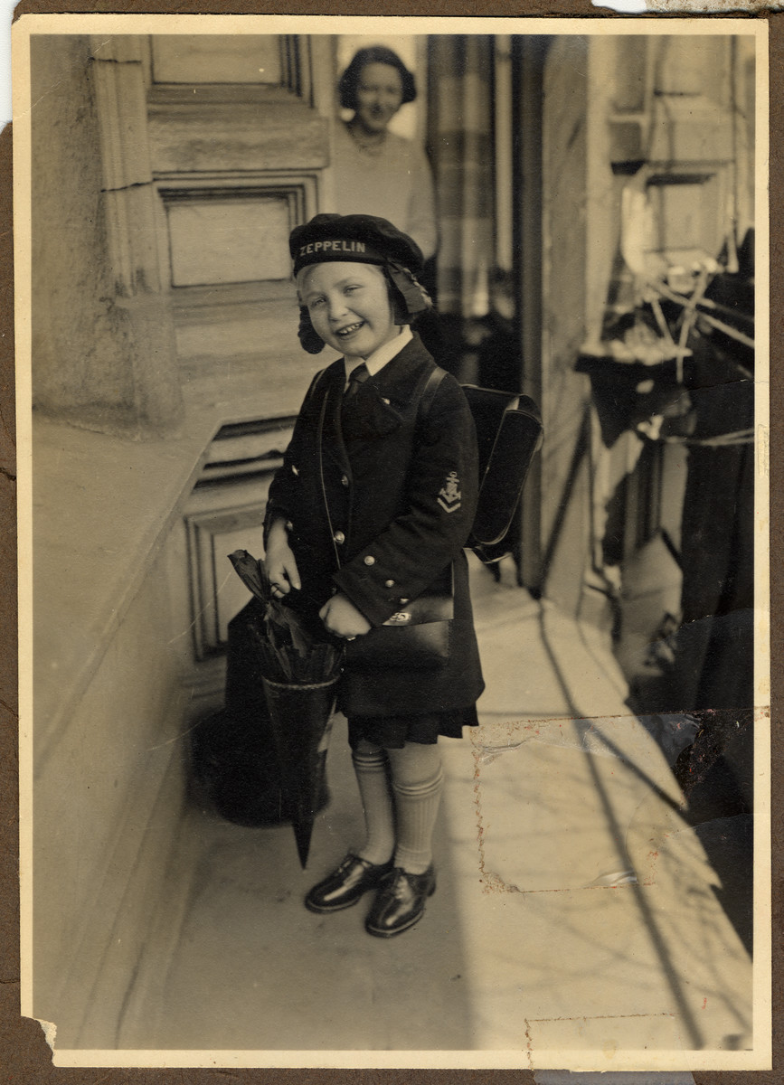 Helga Bujakowski leaves home carrying a back pack and cone filled with treats on her first day of school.  Her mother, Augusta, is pictured in the background.