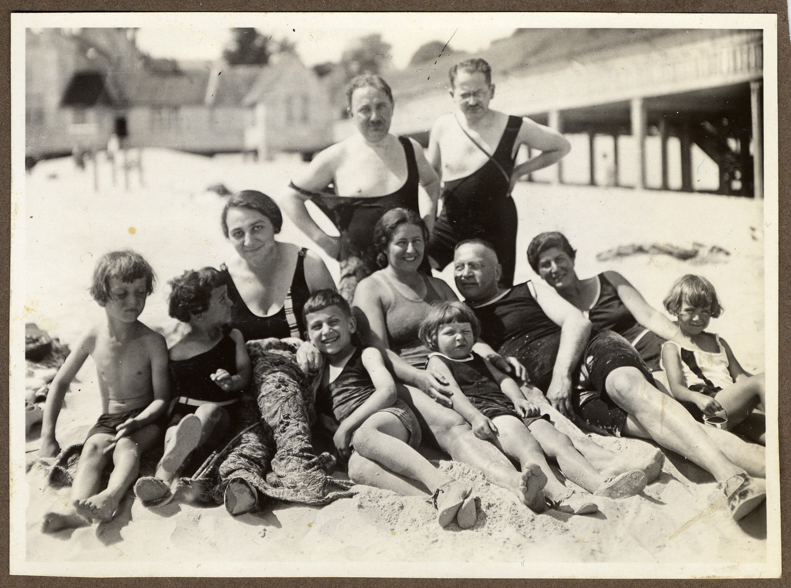 Three German-Jewish families relax on a beach in Heringsdorf on the Baltic Sea.  Pictured from left to right are Werner, Fritz Kohn, Karl-Heinz Kohn, their mother Lisbeth Kohn, Augusta Brager Bujakowski, Helga Bujakowski, Dr. Rudolph Kohn, mother of Lulu and Werner and Lulu.  Standing in back are the father of Lulu and Werner and Dr. Hans Adolf Bujakowski.