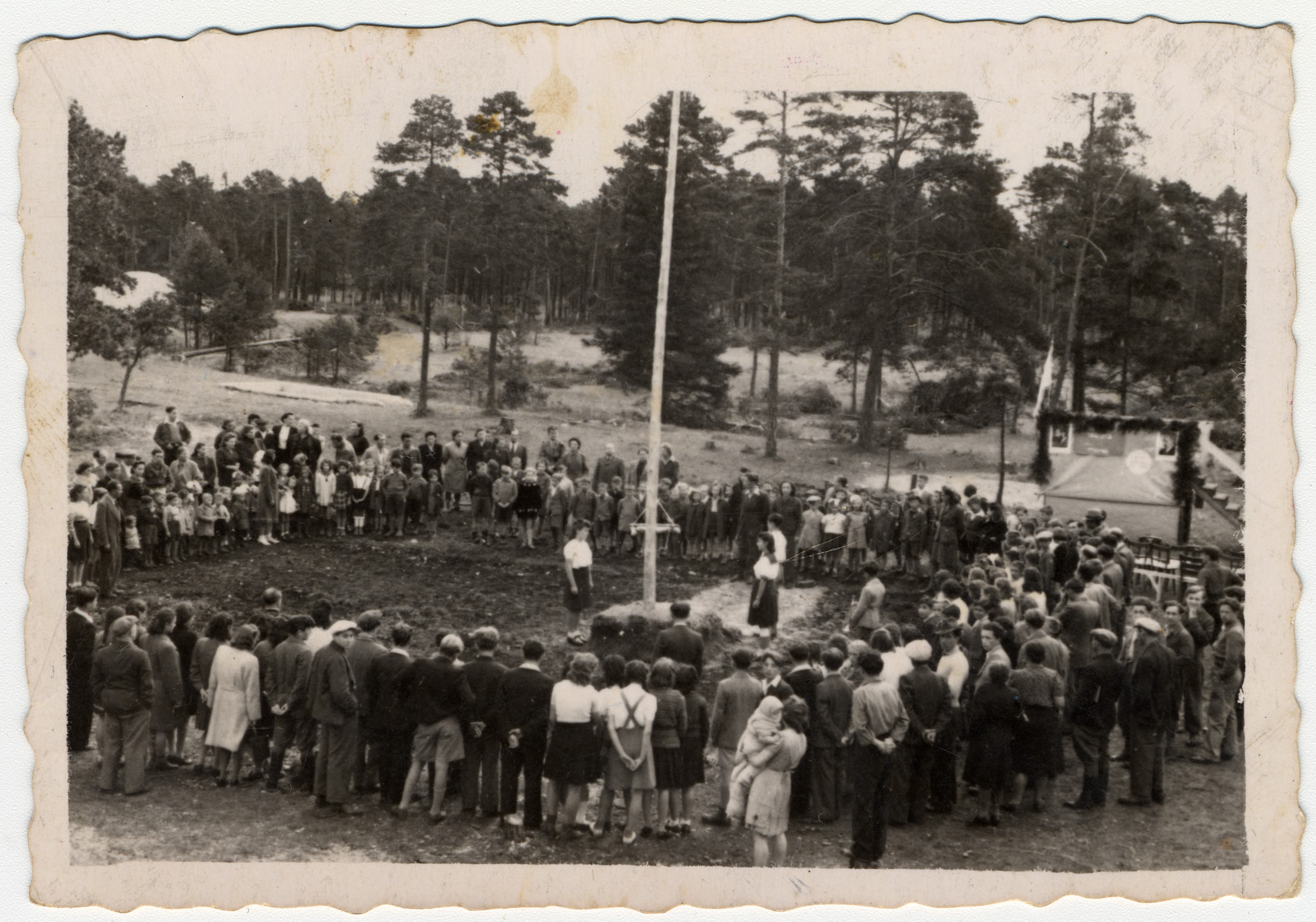 Tarbut School students in the Foehrenwald D.P. camp gather in a circle around a flag pole, celebrating the new year.