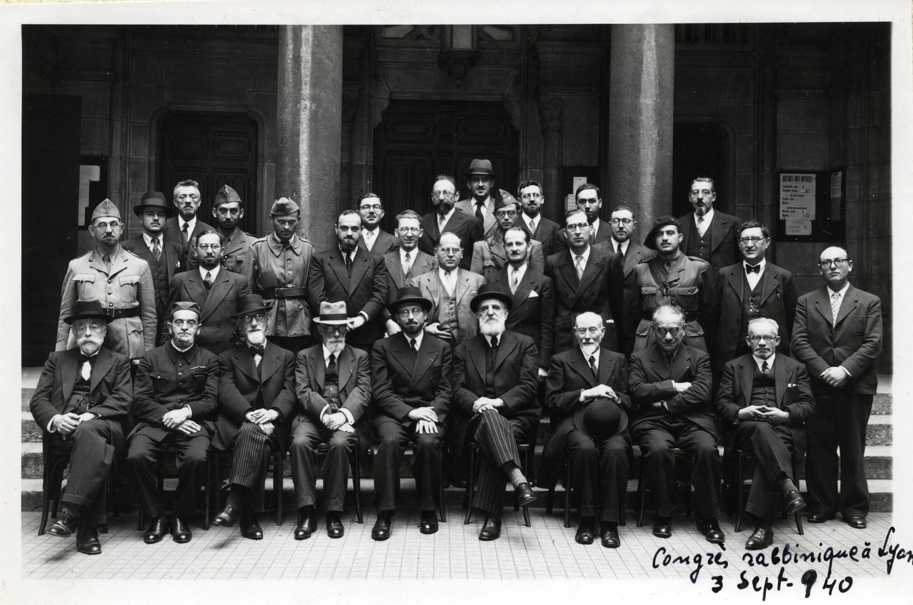 Group portrait of participants in a rabbinical assembly in Lyon.  Among those pictured is Rabbi Jacob Kaplan (first row fifth from the left), Chief Rabbi of France, Isaï Swartz (first row, sixth from the left), Rabbi Moise Cassorla (second row, second from the left), and Rabbi David Feuerwerker (second row, fourth from the left).