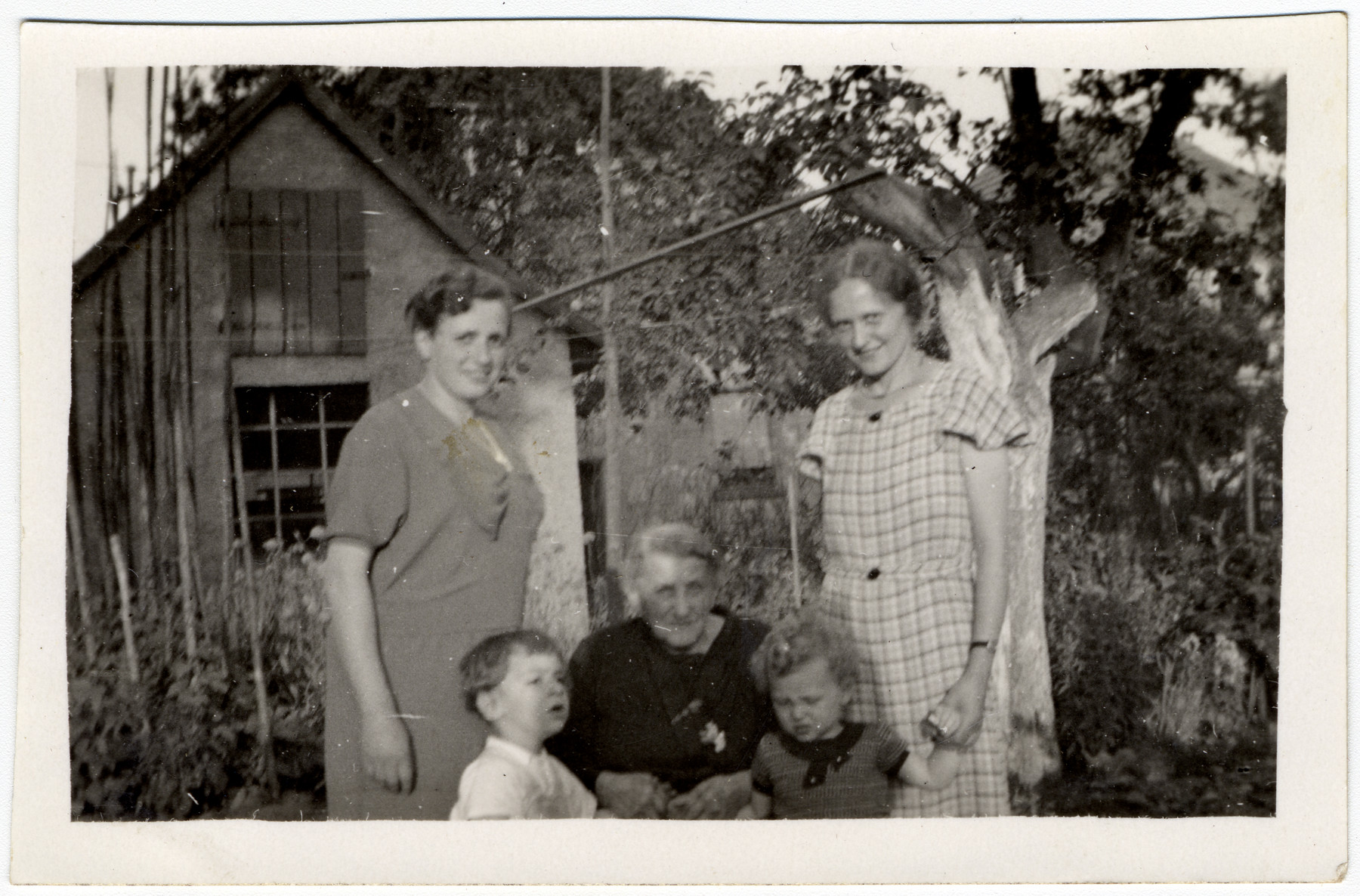 Members of the Wetzler and Weilheimer family pose outside in a garden.  Pictured in the center is the grandmother of Lilly Weilheimer.  Lilly Weilheimer is standing on the right holding the hand of either Richard or Ernst.