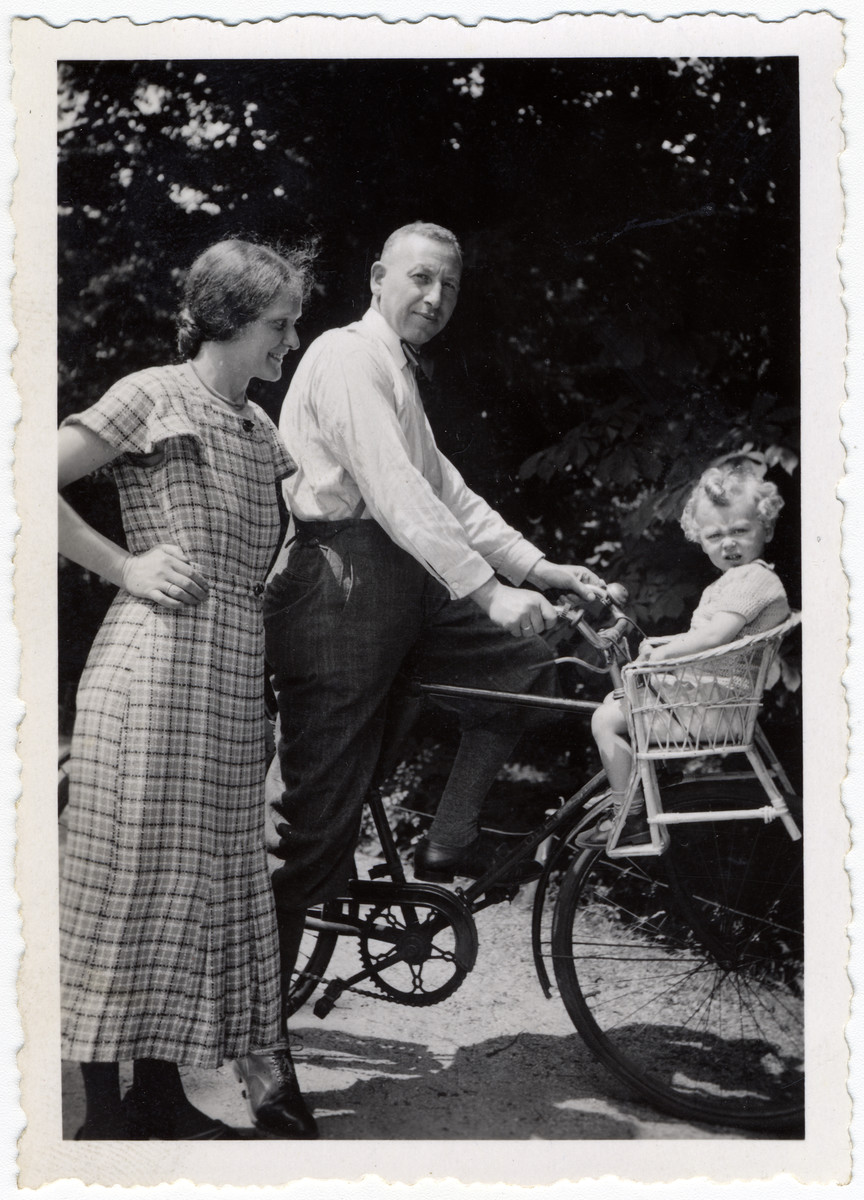 Max Weilheimer takes his son Richard for a ride on his bicycle while his wife Lilly looks on.