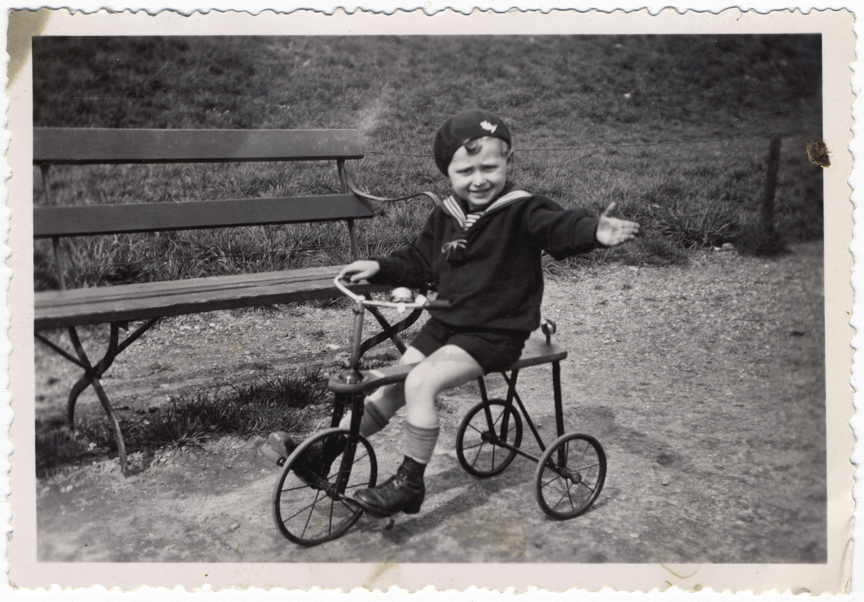 Richard Weilheimer rides his tricycle on a path in a park.
