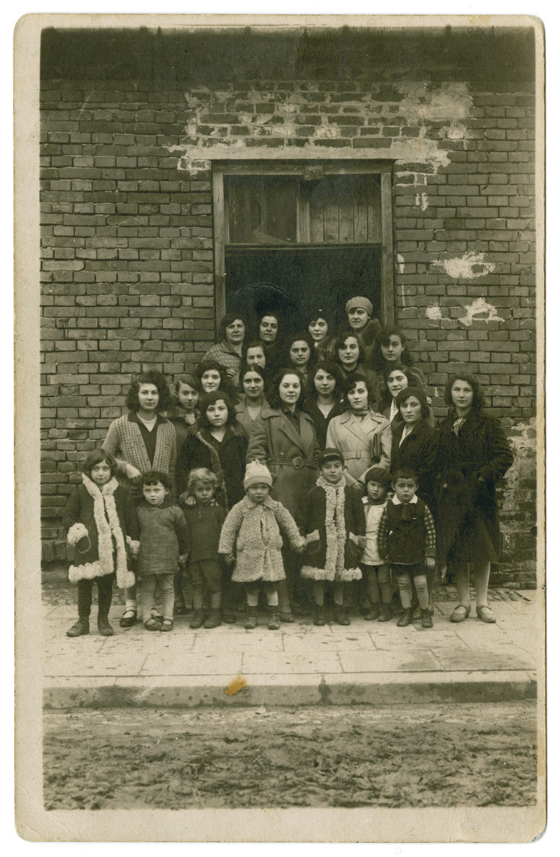 Group portrait of young women and small children standing by the entrance to a building.    Jetta Kilmanowicz is pictured in the second row, third from the right in the light colored coat.