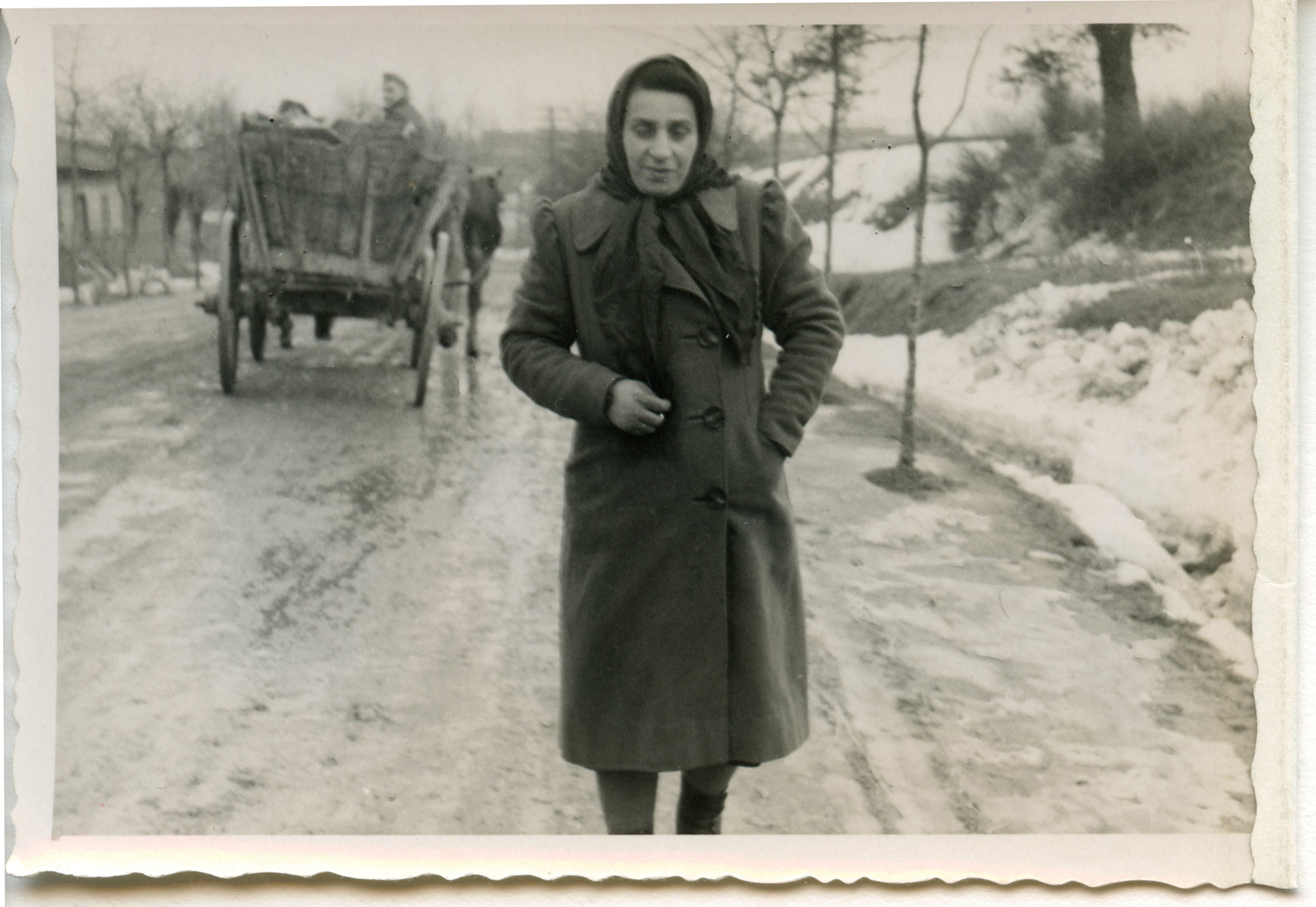 A woman walks down a snowy road [perhaps in Osieciny].
