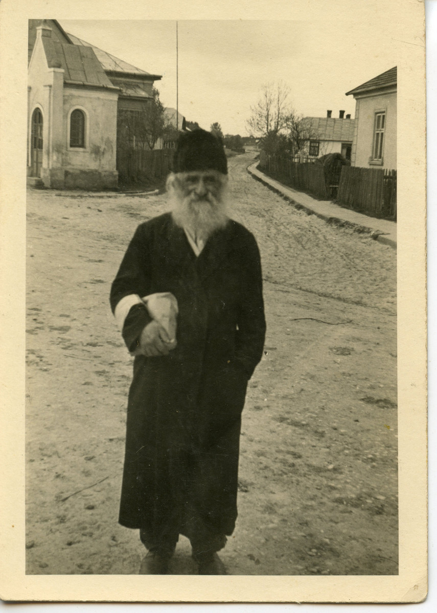 An elderly religious Jew wearing an armband carries a  bundle in an otherwise deserted road.