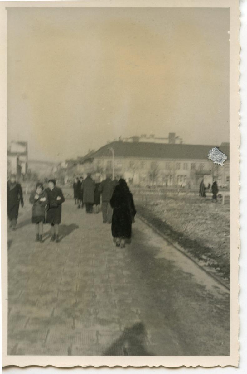 Women walk down a Polish street [perhaps in Osieciny].