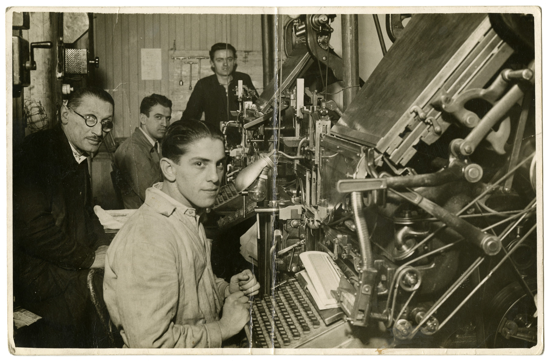 Workers operate the presses of the Goldstuecker printing press owned and operated by the Gero family.  Akos Gero is pictured in the back, second from the left in a grey coat.